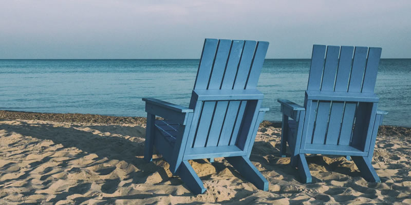 Two lawn chairs on the beach